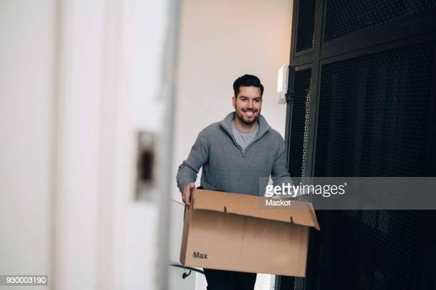 smiling man carrying cardboard box while walking by metal grate in house - tragen stock-fotos und bilder