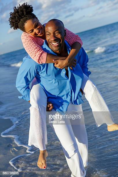Smiling man carrying female on beach
