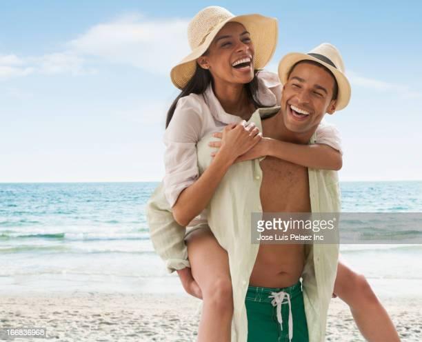 smiling man carrying girlfriend on beach - heteroseksueel koppel stockfoto's en -beelden
