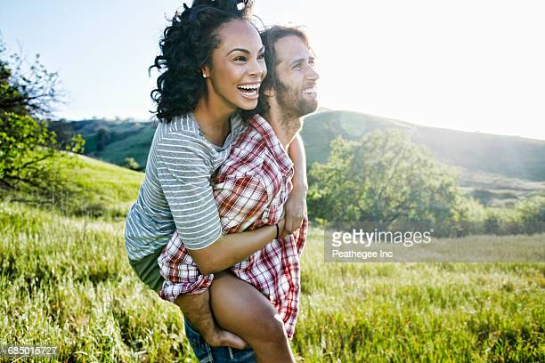 smiling man carrying girlfriend piggyback on hill - multiculturalism stock pictures, royalty-free photos & images