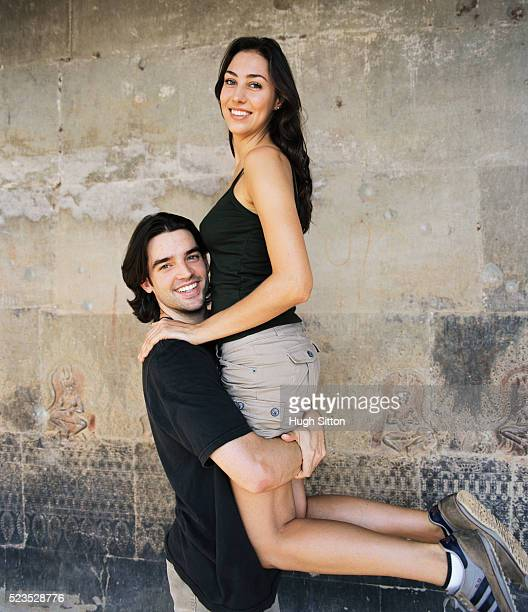 smiling man carrying woman at temple - hugh sitton stock pictures, royalty-free photos & images
