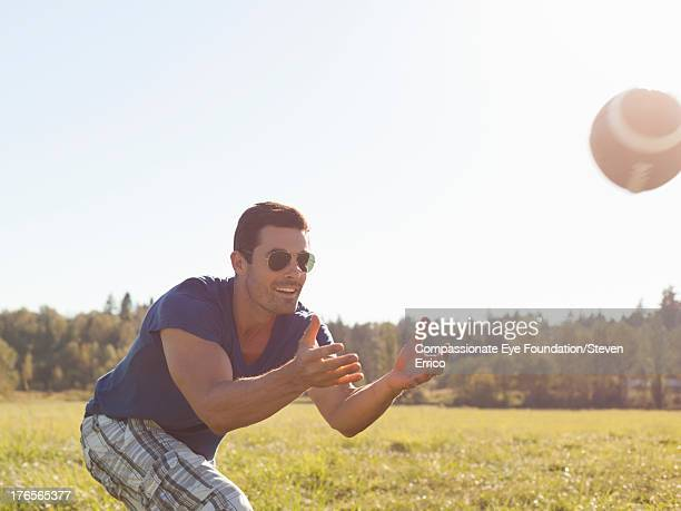 Smiling man catching football in field