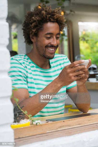Smiling man checking his smartphone at the bar in a cafe