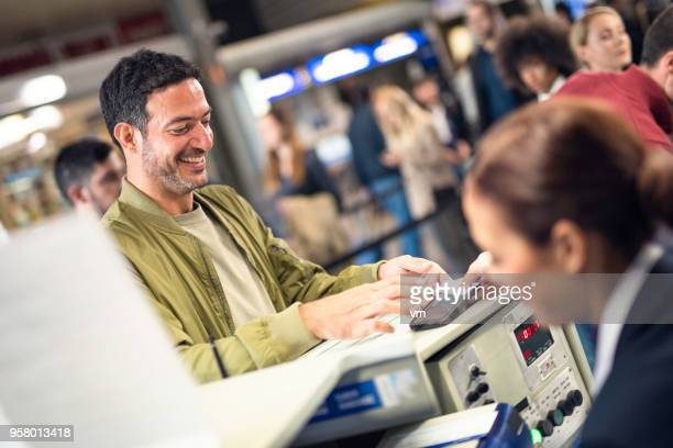 Smiling man checking in at an airport counter