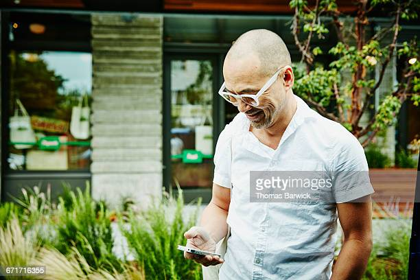 Smiling man checking messages on smartphone