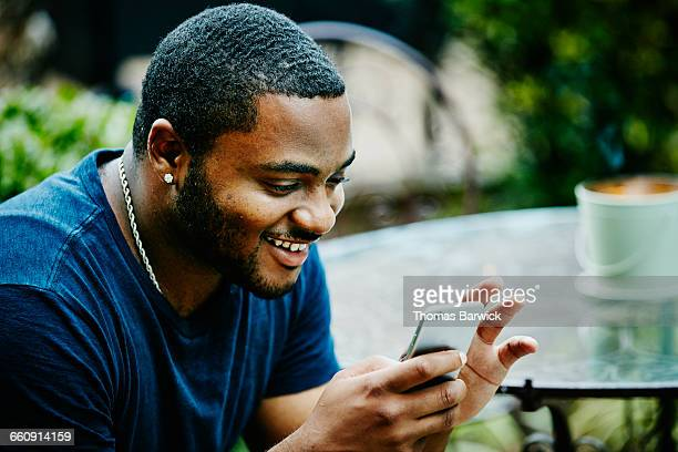 Smiling man checking smartphone during party