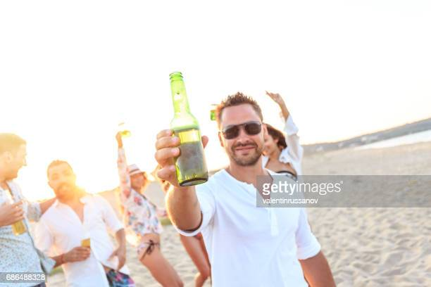 Smiling man cheering, drinking beer with friends on beach