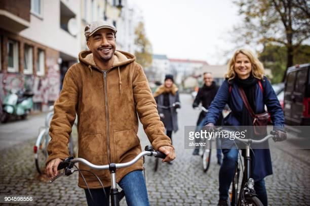 Lächelnd Mann Radfahren mit Freunden auf Stadtstraße