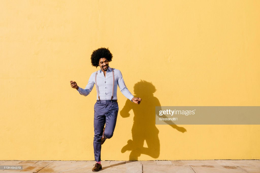 Smiling man dancing in front of yellow wall : Stock Photo