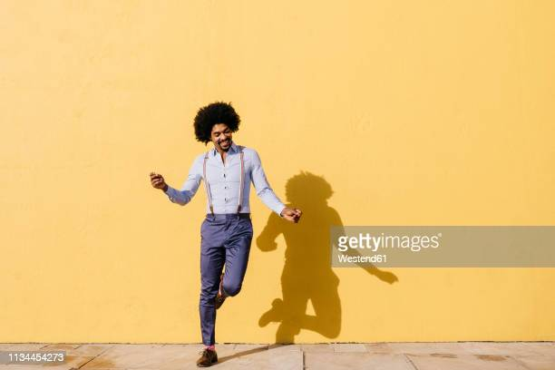 smiling man dancing in front of yellow wall - bewegung stock-fotos und bilder