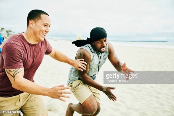 smiling man defending opposing player going out for pass during football game on beach - only mid adult men stock pictures, royalty-free photos & images