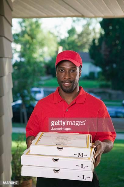 Smiling man delivering pizzas