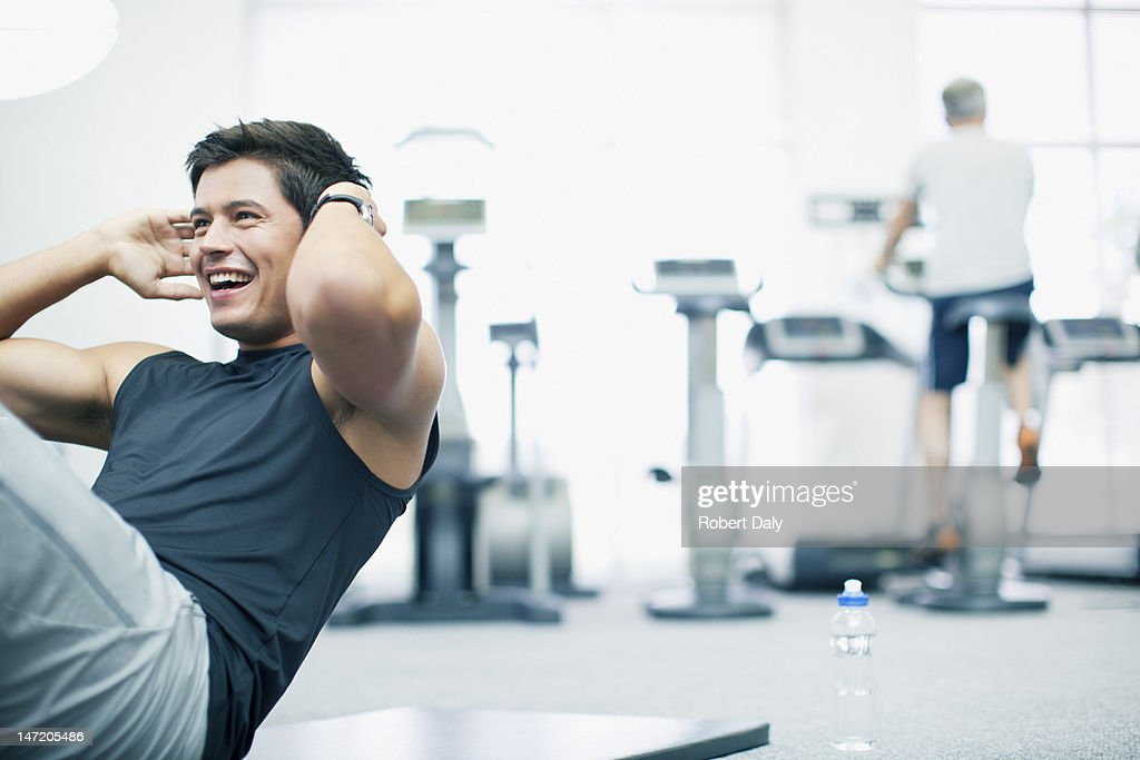 Smiling man doing sit-ups in gymnasium : Stock Photo