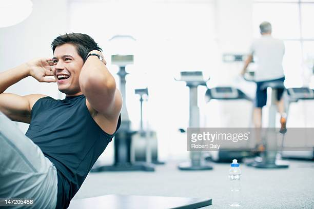 smiling man doing sit-ups in gymnasium - strength training stock pictures, royalty-free photos & images