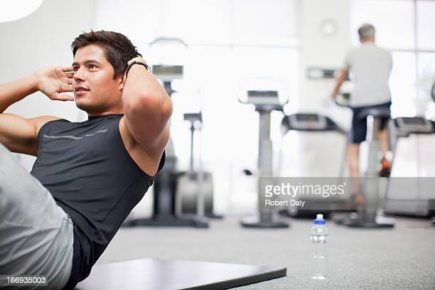 Smiling man doing sit-ups in gymnasium