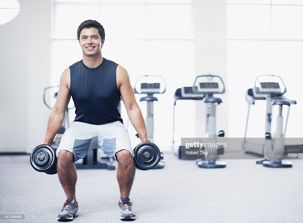 Smiling man doing squats with dumbbells in gymnasium : Stock Photo