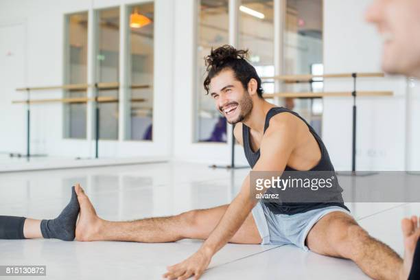smiling man doing stretching in ballet studio - doing the splits stock photos and pictures