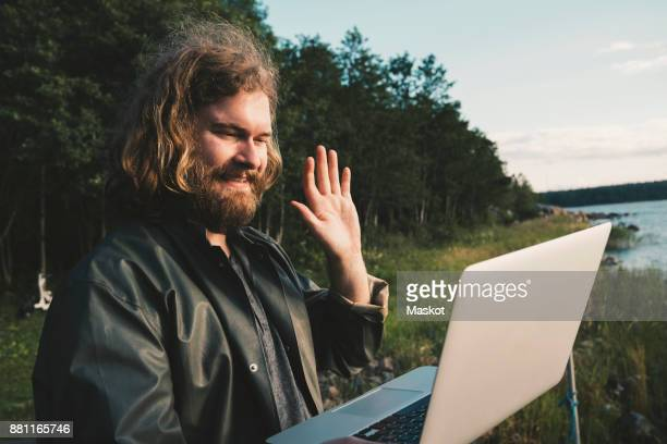 smiling man doing video call on laptop against forest - waving gesture stock photos and pictures