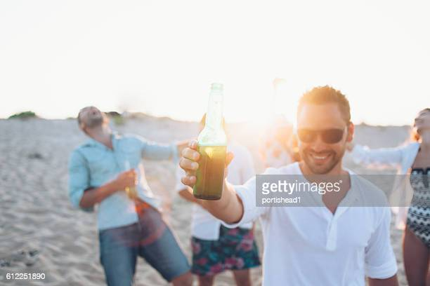 Smiling man drinking beer on the beach