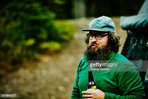 Smiling man drinking beer while camping in woods