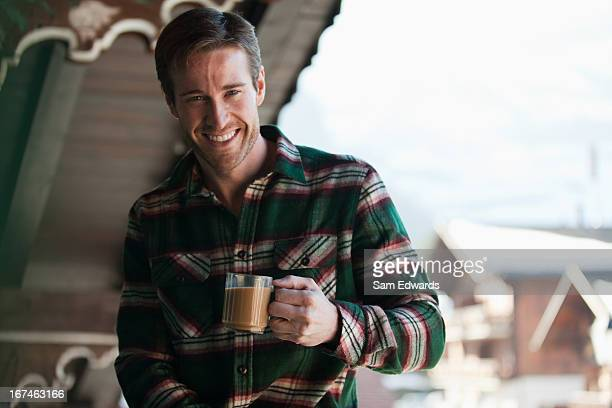 smiling man drinking coffee on cabin porch - plaid stock pictures, royalty-free photos & images