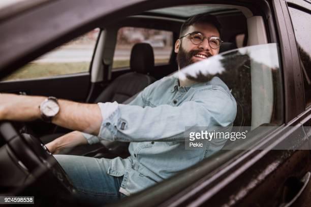 Lächelnder Mann im Auto fahren