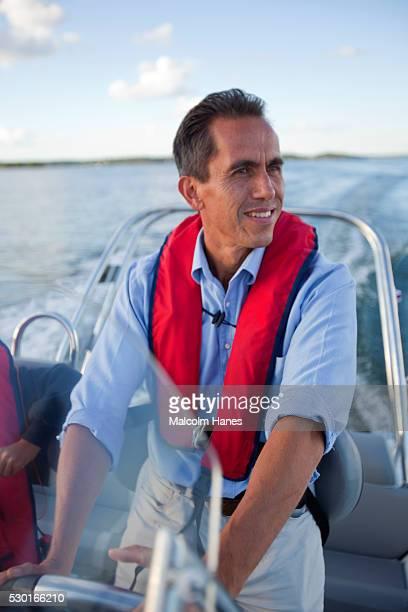 Smiling man driving motorboat