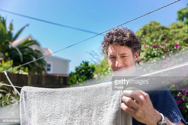 Smiling man drying towel in yard