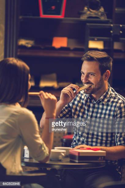 Smiling man eating cookie while spending time with his girlfriend.
