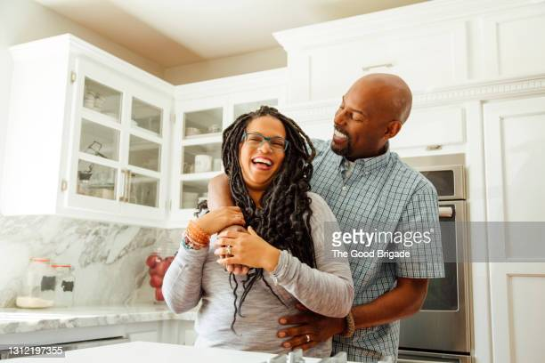 smiling man embracing female partner in kitchen at home - lifestyle stock pictures, royalty-free photos & images