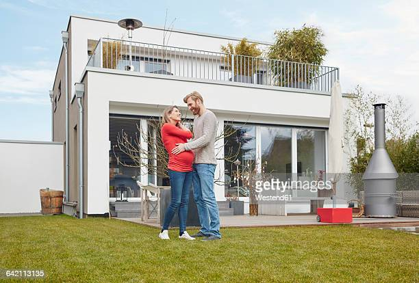 Smiling man embracing pregnant woman in garden