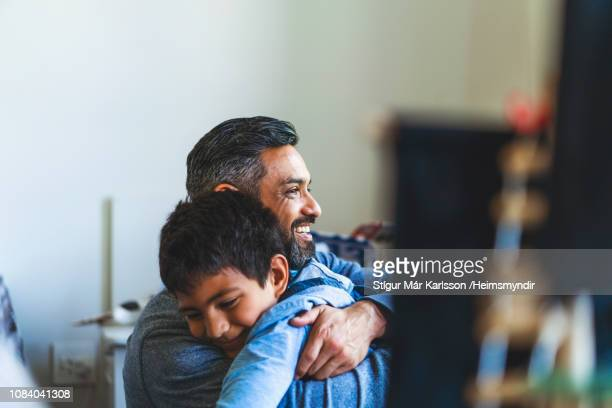 smiling man embracing son in bedroom at home - one parent stock pictures, royalty-free photos & images