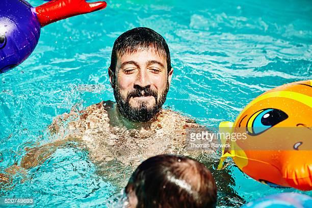 smiling man emerging from underwater in pool - framträdande bildbanksfoton och bilder