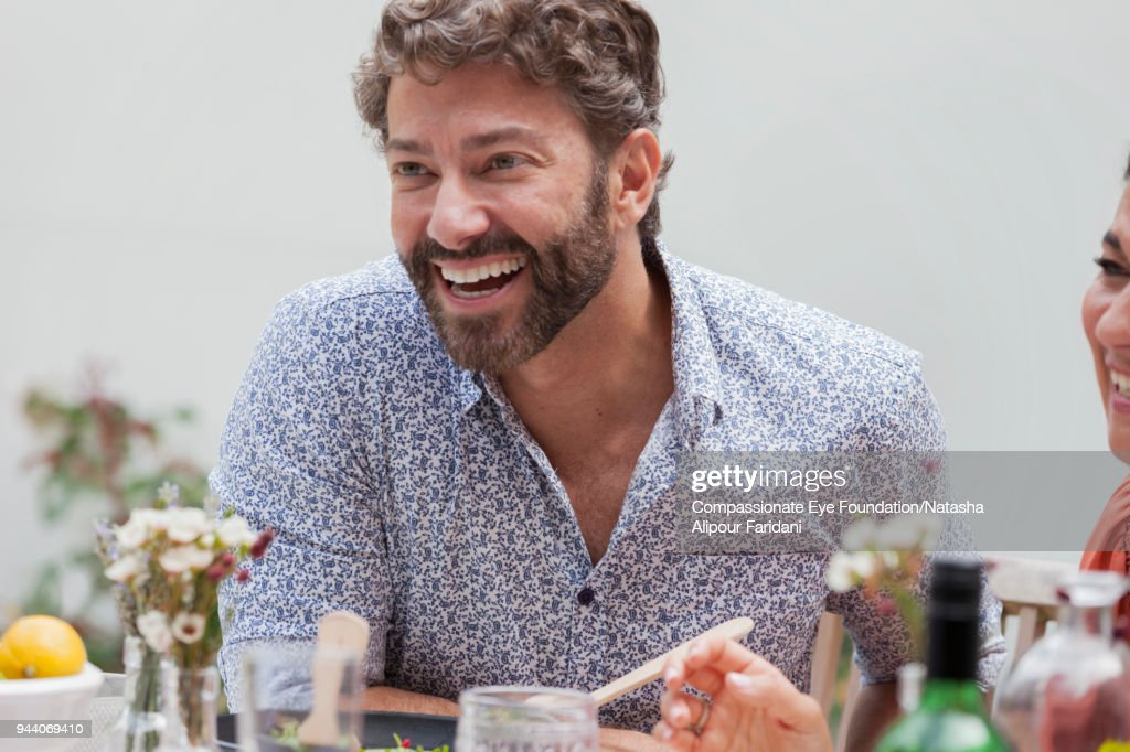 Smiling man enjoying lunch with friends on patio : Stock Photo