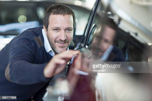 Smiling man examining new car at car dealership