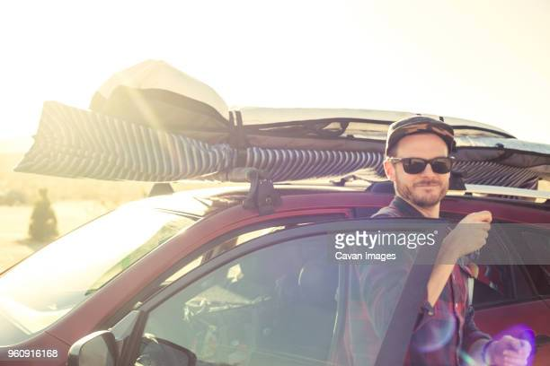 smiling man getting out of loaded car against clear sky on sunny day - 降り立つ ストックフォトと画像