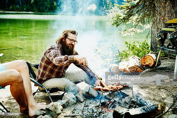 Smiling man grilling chicken on fire while camping