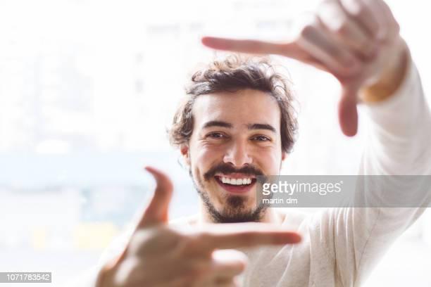 mão de homem a sorrir moldação - dedos fazendo moldura - fotografias e filmes do acervo