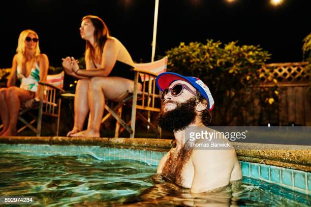 Smiling man hanging out in pool during backyard party with friends on summer evening