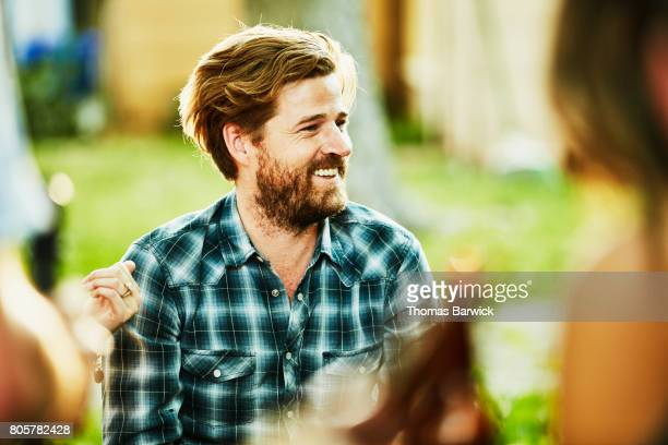 smiling man hanging out with friends during backyard barbecue on summer evening - southern usa stock pictures, royalty-free photos & images
