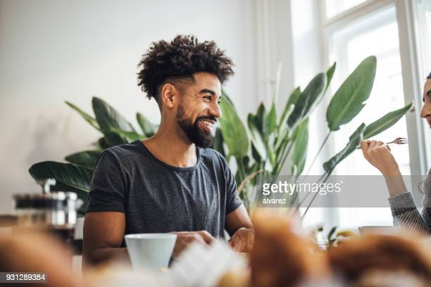 Smiling man having breakfast with woman at home