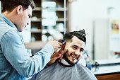 smiling man having hair trimmed barber