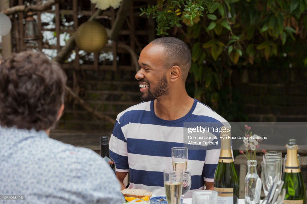 Smiling man having lunch with friends at garden patio table : Stock Photo