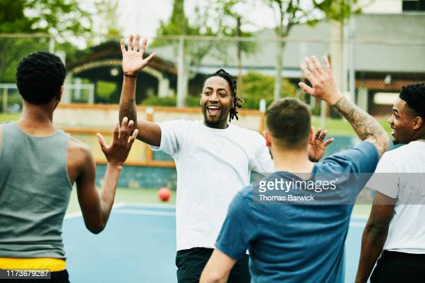smiling man high fiving teammates after winning dodgeball game - team sport stock pictures, royalty-free photos & images