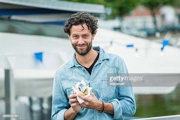 Smiling man holding a fish sandwich
