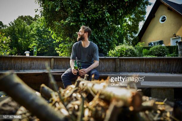 smiling man holding beer bottles sitting on bench in garden - wochenendaktivität stock-fotos und bilder