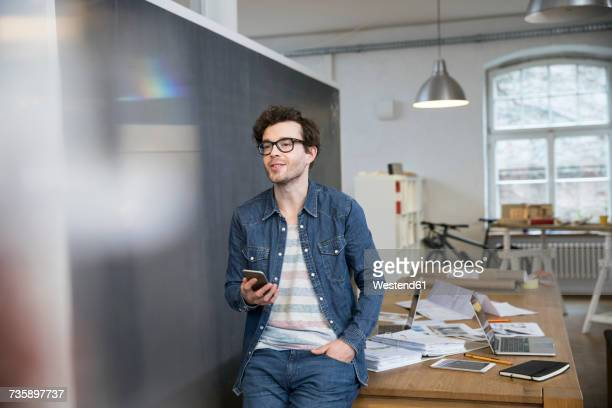 Smiling man holding cell phone in office