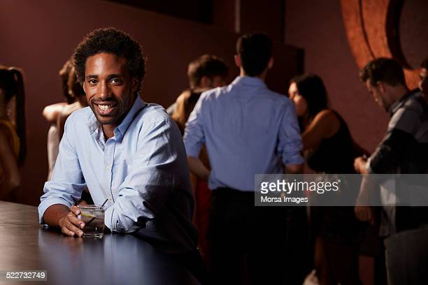 Smiling man holding drink at counter in nightclub