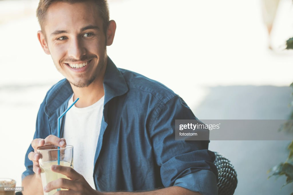 Smiling man holding glass of lemonade and straw : Stock Photo