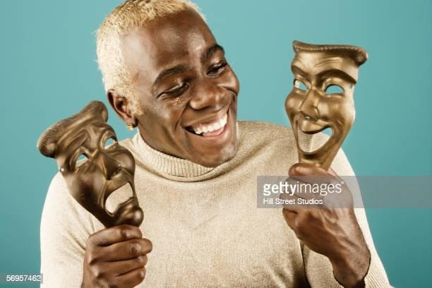 smiling man holding greek drama masks - schauspieler stock-fotos und bilder